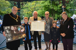 Geoff and Jacquie Stevens (centre) receiving presentations from Cllr Steve Flitter his wife Ann and their grandchildren Zach and Isabel