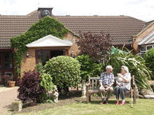 Elderly couple sitting on bench in a garden