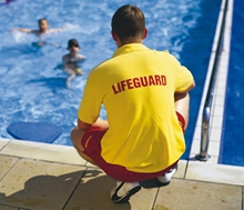 Lifeguard in yellow t-shirt and red shorts supervising a swimming pool