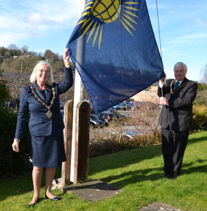 Cllrs Carol Walker and Peter Slack raising the Commonwealth Flag at Matlock Town Hall