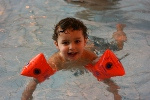 Young boy with red arm bands learning to swim
